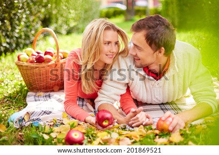 Happy young couple with ripe apples looking at one another while having rest in park - stock photo