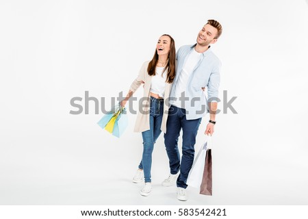 Happy young couple with shopping bags embracing and looking away isolated on white