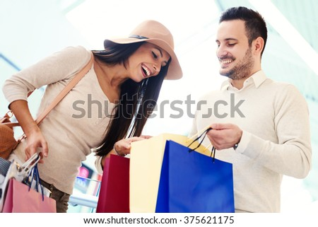 Happy young couple with shopping bags.Image taken inside a shopping mall. - stock photo