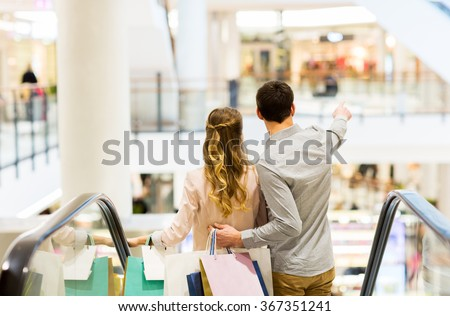happy young couple with shopping bags in mall - stock photo