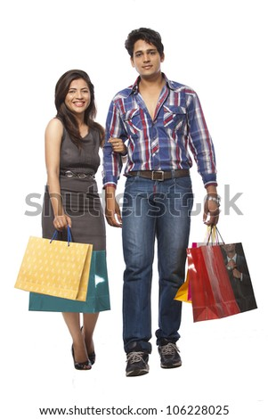 Happy young couple with shopping bags over white background - stock photo