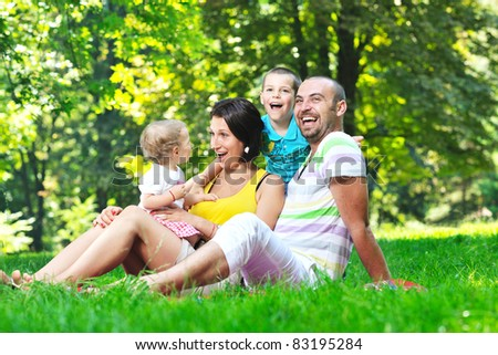 happy young couple with their children have fun at beautiful park outdoor in nature - stock photo