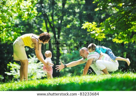 happy young couple with their children have fun at beautiful park outdoor in nature