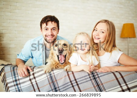 Happy young couple with their daughter and dog looking at camera - stock photo