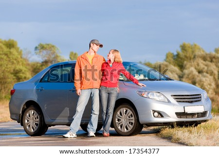 Happy young couple with their new car. - stock photo