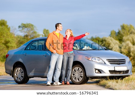 Happy young couple with their new car. Woman show something by hand. Looking at something above. - stock photo