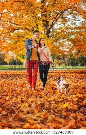 Happy young couple with two cute dogs walking in park on nice autumn day - stock photo