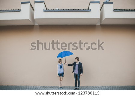 Happy young couple with umbrella - stock photo