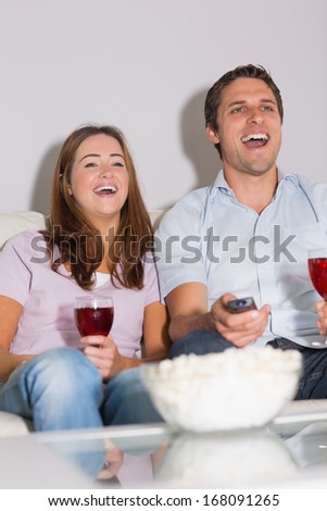 Happy young couple with wine glasses and popcorn enjoying a movie on sofa at home - stock photo