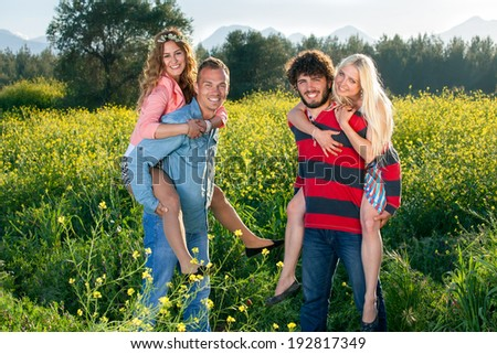 Happy young couples enjoying nature as the two smiling young men give their attractive girlfriends a piggy back ride through a yellow rapeseed field - stock photo
