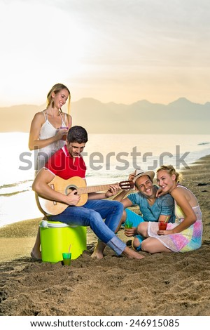 Happy Young Couples Enjoying their Drinks at the Beach While Playing Guitar Instrument. - stock photo