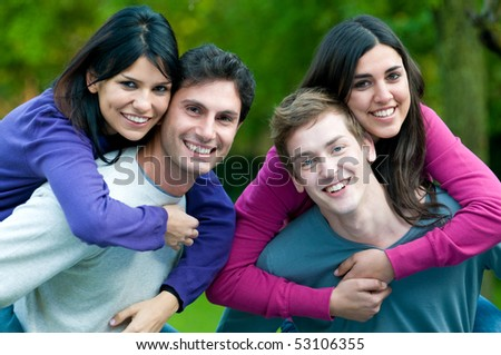 Happy young couples smiling and playing piggyback together with fun outdoor