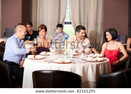 happy young couples toasting restaurant table