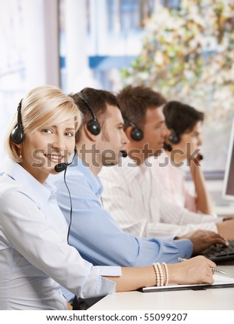 Happy young customer service operator talking via headset, smiling people in background.? - stock photo