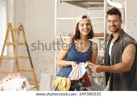 Happy young diy couple building new home, choosing paint colors, from color scale. - stock photo