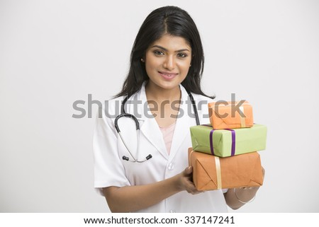 Happy young Doctor with a stethoscope. Holds a a gift box. Isolated on white background - stock photo
