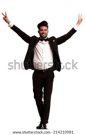 happy young elegant man wearing tuxedo celebrating success with hands up in the air - stock photo