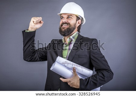 Happy young engineer celebrating with arm raised, concept of successful construction, over gray background - stock photo