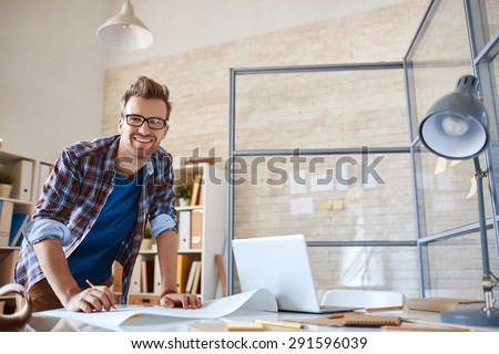 Happy young engineer looking at camera in office - stock photo