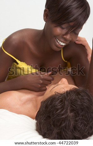 Happy young ethnic black African American woman and mid aged Caucasian man in bed interacting and making love - stock photo