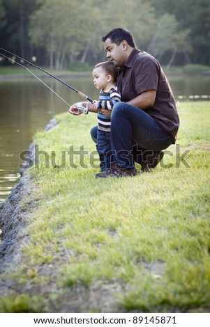 Happy Young Ethnic Father and Son Fishing at the Lake. - stock photo