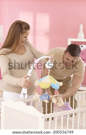 Happy young expecting couple equipping baby's cot. - stock photo