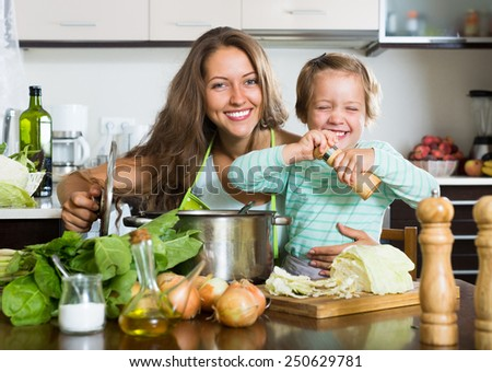 Happy young  family cooking soup  at home kitchen - stock photo
