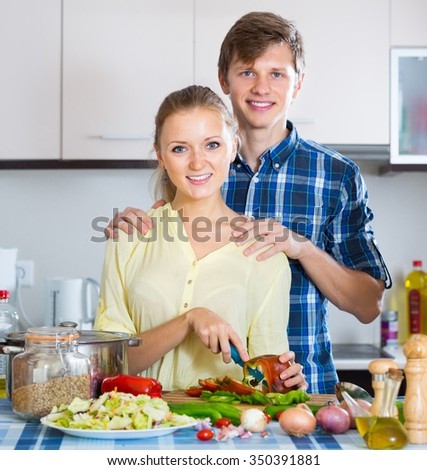 Happy young family couple cooking vegetables in domestic kitchen