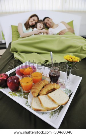 happy young family eat breakfast in bed at morning - stock photo