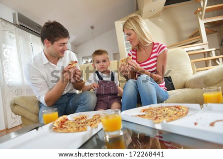 happy young family eating tasty pizza with cheesa and dring healthy and fresh orange juice - stock photo