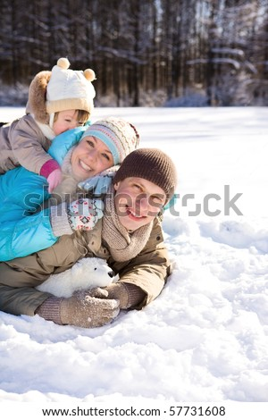 Happy young family enjoying their weekend in a winter park - stock photo