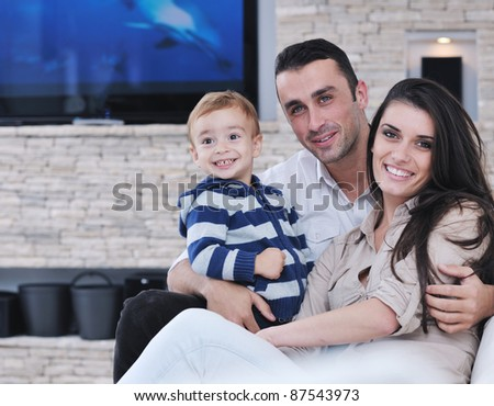 happy young family have fun and relaxing at new home with modern lcd tv in background - stock photo