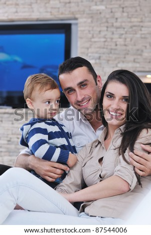 happy young family have fun and relaxing at new home with modern lcd tv in background