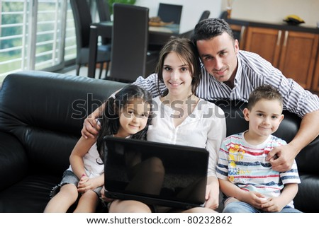happy young family have fun and working on laptop at modern  home livingroom indoor - stock photo
