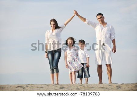 happy young family have fun on beach and showing home sign with connected hands while protecting children - stock photo