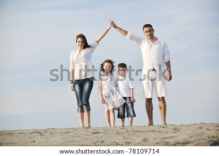 happy young family have fun on beach and showing home sign with connected hands while protecting children
