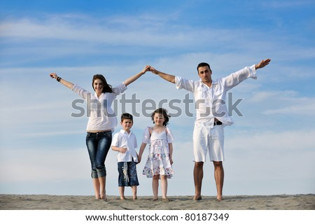 happy young family have fun on beachand showing home sign with conncected hands while protecting childrens - stock photo