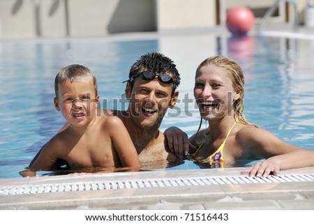 happy young family have fun on swimming pool  at summer vacation - stock photo