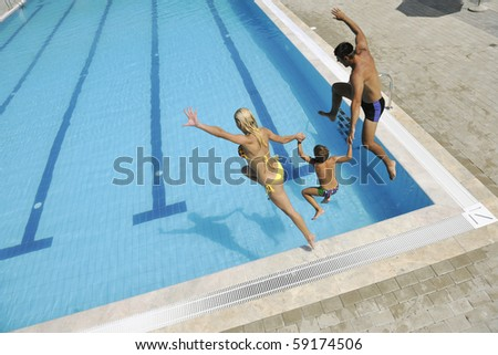 happy young family have fun on swimming pool  at summer vacation running and jumping in the pool - stock photo
