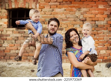 Happy young family have fun together in nature by the old brick house - stock photo