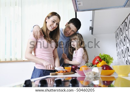 happy young family have lunch time with fresh fruits and vegetable food in bright kitchen - stock photo