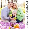 happy young family having a picnic in the park on a summer day (focus on the child) - stock photo