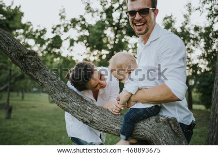 Happy young family having fun, bowl, rising up, piggyback ride their child in park on summer sunset