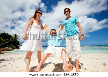 Happy young family having fun on tropical beach