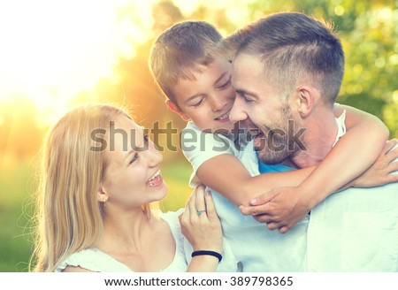 Happy young family having fun outdoors. Joyful young family father, mother and little son playing together in spring park. Mom, Dad and kid laughing and hugging, enjoying nature outside. Piggyback - stock photo