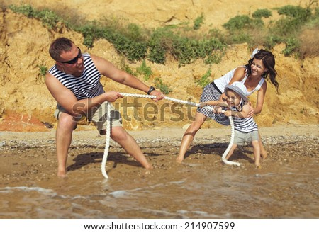 Happy young family having fun outdoors pulling a rope. Summer vacation  - stock photo