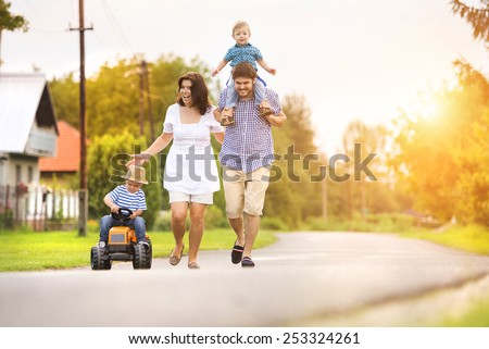 Happy young family having fun outside on the street of a village - stock photo