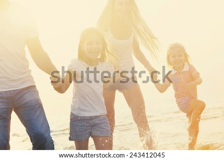 Happy young family having fun running on beach at sunset. Toned photo. Family traveling concept - stock photo