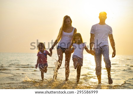 Happy young family having fun running on beach at sunset. Toned photo. Family traveling concept. No effects - real sun - stock photo