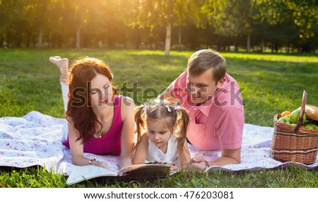 Happy young family having picnic at meadow at summer day. Mother reading a book with her little daughter